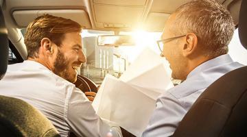 Dos hombres con papeles en un coche